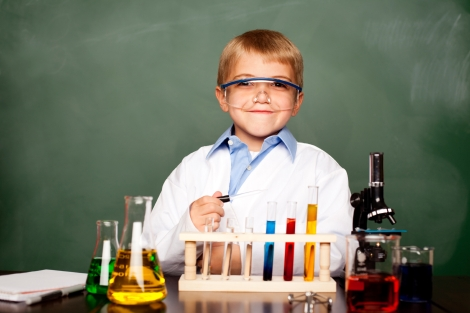 Little boy wearing lab coat and goggles, with beakers and test tubes of colored liquids