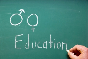 "Male and female symbols drawn on a chalkboard with ""education"" written below them"