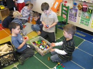 Preschool-age boys in a classroom setting gathered around a bucket of Legos