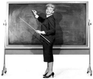 Black and white old fashioned picture of female teacher at a blackboard