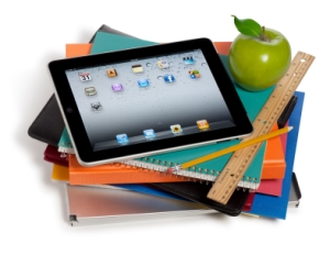 Stack of notebooks and school supplies with an ipad and apple on top of the pile