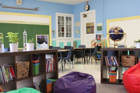 Neat, well organized classroom with colored beanbag chairs, blue walls, yellow trim, plants, and good lighting