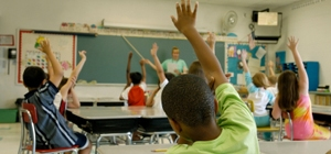 elementary classroom of engaged students raising their hands