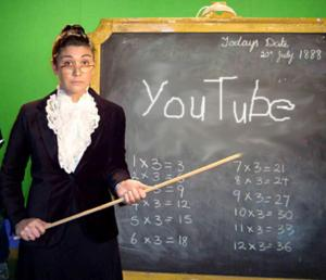 "Woman in a suit in front of a chalkboard that says ""youtube"" on it"