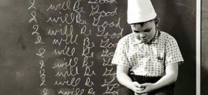 "Black and white photo of young boy wearing dunce hat standing in front of chalk board that says ""I will be good"" written over and over"